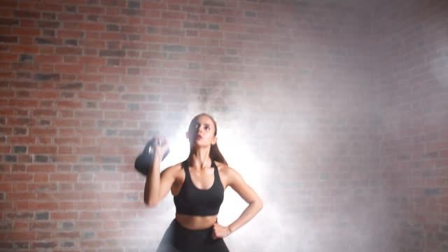 sportowa kobieta z kettlebell szkolenia w siłowni - giria filmów i materiałów b-roll