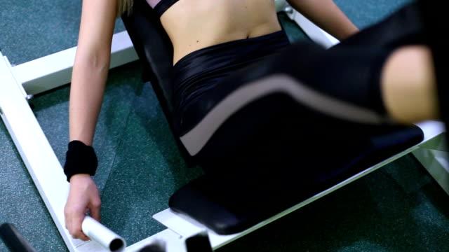 sportive young woman doing strength training on a gym. pumping leg muscles. - donna forzuta video stock e b–roll