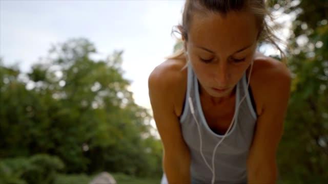 vidéos et rushes de sportive jeune femme jogging en plein air, sentier expérience s'arrête pour reprendre son souffle. concept de mode de vie sain et consciente de corps personnes. - joggeuse