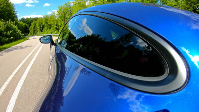 Sports car driving fast on a winding country road, surrounded by lush foliage Driving an elegant and luxurious blue sports car on an empty country road through picturesque scenery on a beautiful sunny day, surrounded by lush foliage sports car stock videos & royalty-free footage