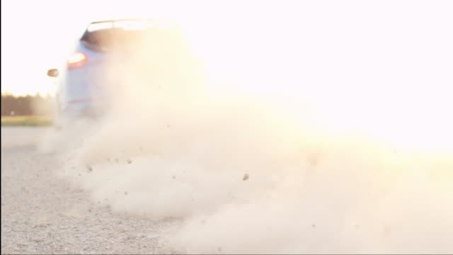 CLOSE UP Sports car takes off from dirt road, raising dust cloud at pink sunset video
