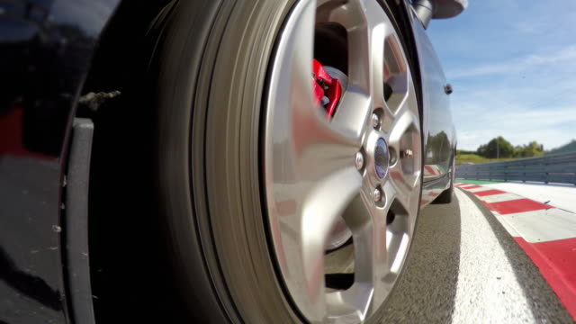 Sports car wheels spinning during a motorsport event competition, driving into pit stop video