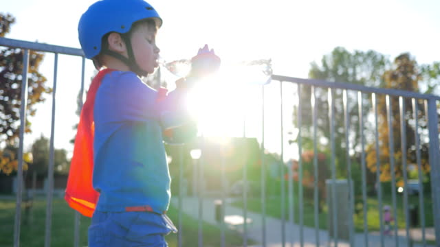 sports child in helmet and rollers drinks pure water from plastic bottle outdoors