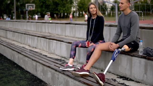 vídeos de stock, filmes e b-roll de casal de esportes relaxante na arquibancada - medicina esportiva