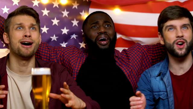 vídeos de stock e filmes b-roll de sports fans in bar waving usa flag, rejoicing national football team victory - liga desportiva