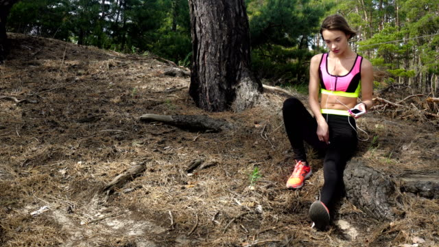 Sports girl listens to music in the forest video
