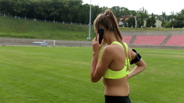 A sports girl speaks on the phone before the jog at the sports stadium video