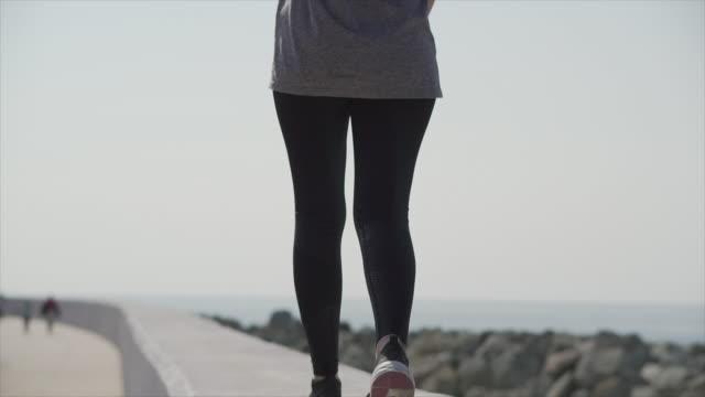 A sports girl walks along the city promenade along the seashore on a sunny day Sport girl walks along the seashore on a sunny day t shirt stock videos & royalty-free footage