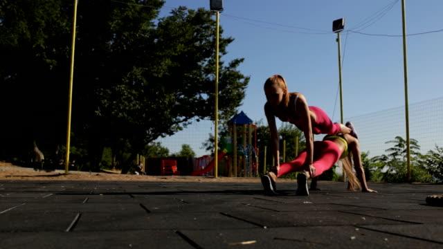 sports girlfriend workout outdoor. they make plank together. - спортивный бюстгальтер стоковые видео и кадры b-roll