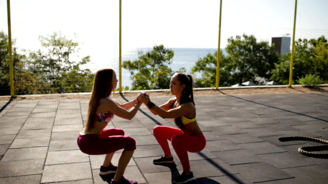 sports girlfriend workout outdoor. they squat together. - спортивный бюстгальтер стоковые видео и кадры b-roll