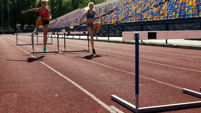 vídeos y material grabado en eventos de stock de chicas deportes fácilmente superar las barreras en pista, selección para la competencia - valla artículos deportivos