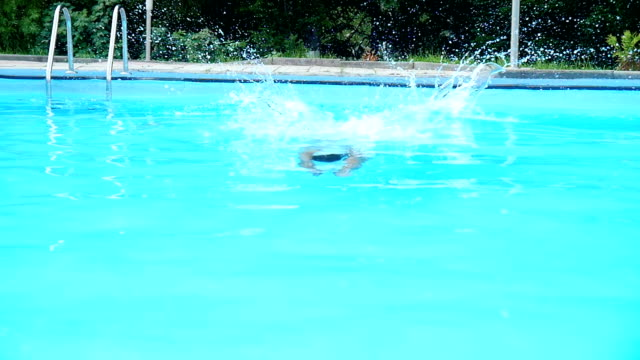 sports guy runs up and dives into the pool.Slow motion video