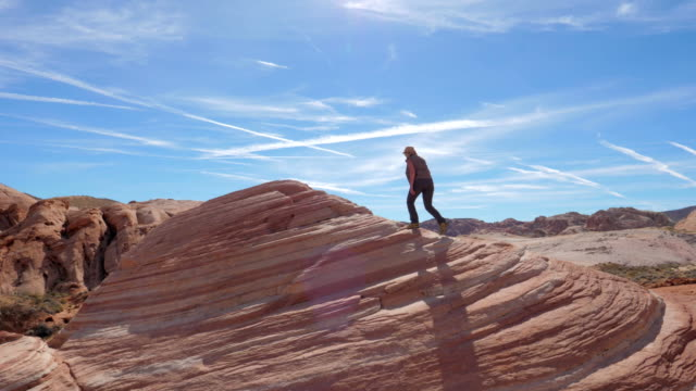 sports hiking woman climbs up the red rock background the sky slow motion 4k - parco nazionale video stock e b–roll