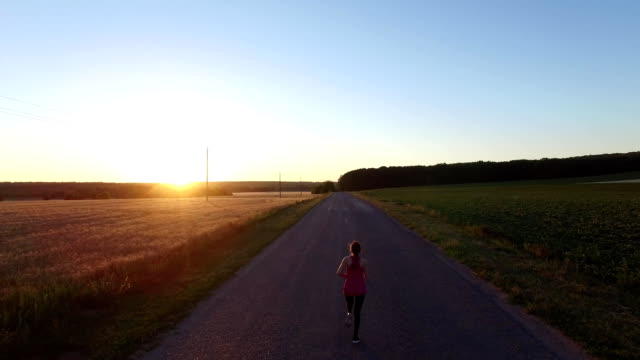 sport jogger kvinna kör en väg nära fältet vid solnedgången - jogging hill bildbanksvideor och videomaterial från bakom kulisserna