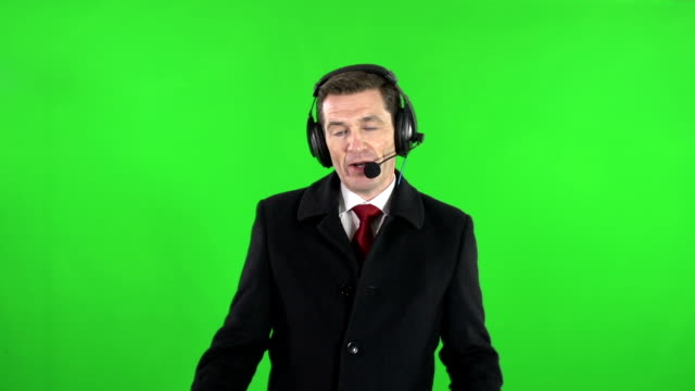 TV / Sports reporter or Commentator with headset microphone on Green Screen video