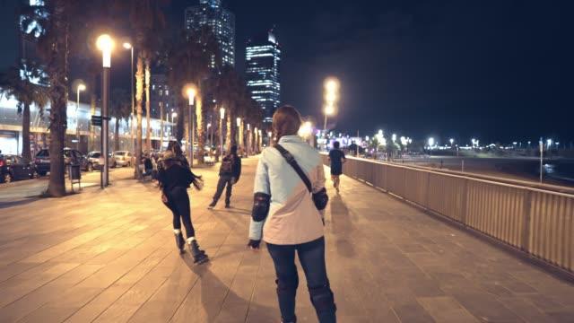 sports roller girl skating at night in the city - łyżwa filmów i materiałów b-roll