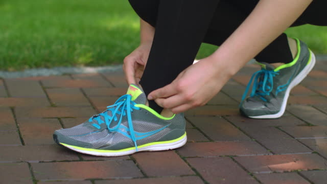 Sports shoes. Woman tying running shoes. Closeup of woman hands tying up shoes video