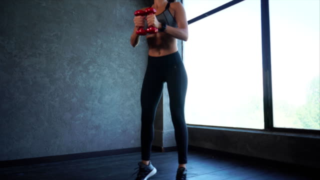 a sports woman doing sit-ups and jumping, she is holding dumbbells - giuntura umana video stock e b–roll