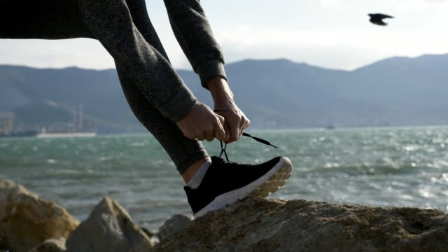 Sports woman getting ready for run tying laces of running shoes on the beach video