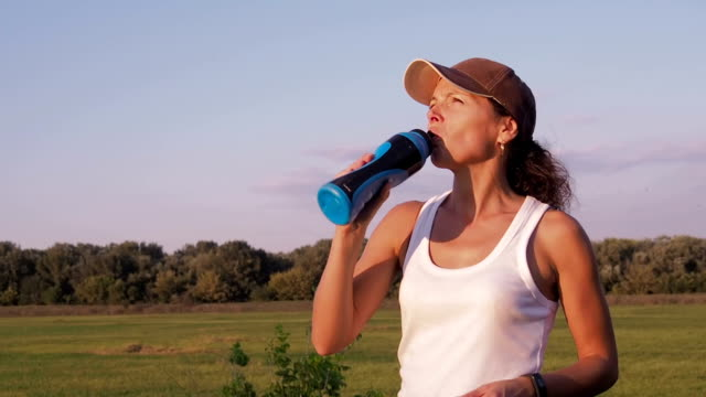 A sports woman is drinking water. A sports woman is drinking water. A woman in nature is doing sports with a fitness bracelet. panting stock videos & royalty-free footage