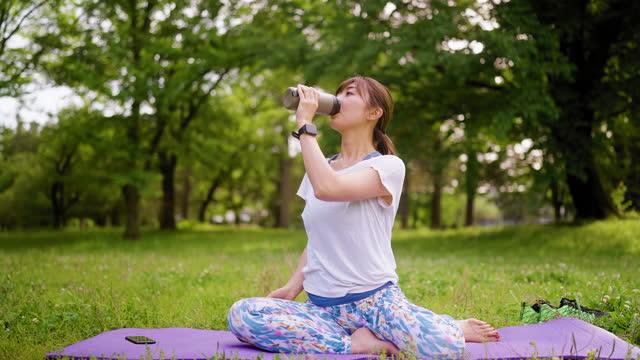 スポーツトレーニングや自然の中で飲料水から休憩を取るスポーツ女性 - ヨガ点の映像素材/bロール