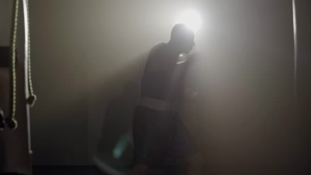 Sportsman boxing shadow in lense flare in haze. Silhouette of confident young Caucasian boxer training in fog in backlight. Concept of competitive sport, martial arts, strength, lifestyle.