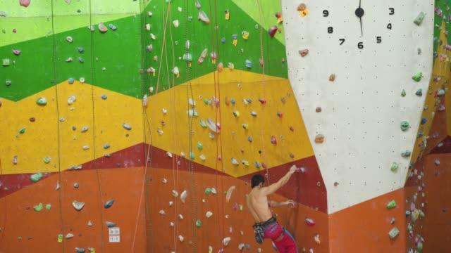 vídeos de stock, filmes e b-roll de montanhista do desportista que move-se acima na rocha íngreme - penedo