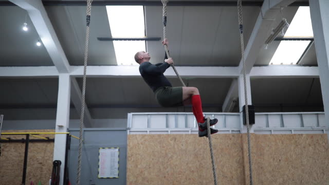 sportsman climbing up gymnastic rope and returning upside down - inerpicarsi video stock e b–roll