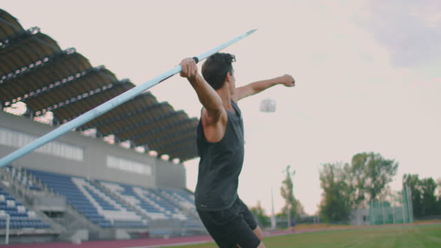 sportsman doing javelin throw on athletic ground. male athlete throwing the javelin in the olympic stadium. athlete in sport clothes at athletic sport track in professional stadium - campionato video stock e b–roll