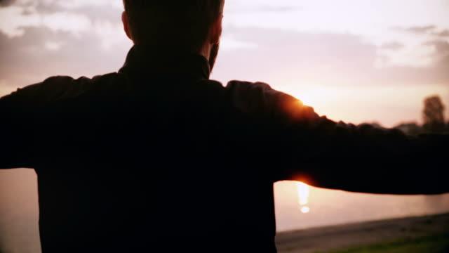 4 k sportsman utövar nära soluppgång morgonen lake. bakifrån hane svängande armar och hoppning. professional passar idrottsman nen - förberedelse bildbanksvideor och videomaterial från bakom kulisserna
