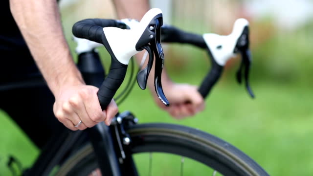 Sportsman grips handlebar of road bicycle. Racking focus close up shot video
