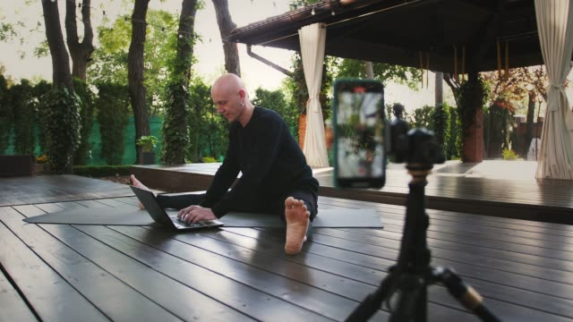 Sportsman in black clothes performing yoga, working on laptop, sitting on mat at inner yard. Shooting himself on video by mobile phone on tripod