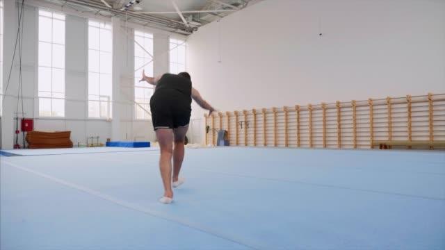 vídeos de stock, filmes e b-roll de um desportista está fazendo um cartwheel e uma volta dupla flip e terras, steadicam. - ginástica