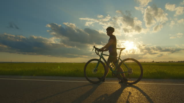 A sportsman is walking along the road with a bicycle. He is looking at his fitness tracker. Training on a bicycle. Green field and sunset in the background. 4k