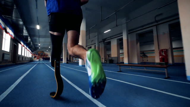 Sportsman jogging, wearing bionic prosthesis, back view. A runner training, wearing leg prosthesis. prosthetic equipment stock videos & royalty-free footage
