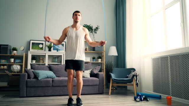 sportsman jumping rope training at home alone wearing sportswear and sneakers - body conscious stock videos & royalty-free footage