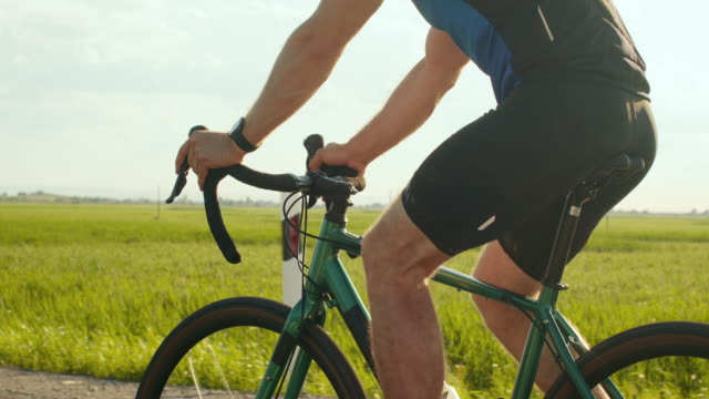 A sportsman on a bicycle is riding along the highway. Close-up of the cyclist's legs. Training on a bicycle. 4K A sportsman on a bicycle is riding along the highway. Close-up of the cyclist's legs. Training on a bicycle. 4K handlebar stock videos & royalty-free footage