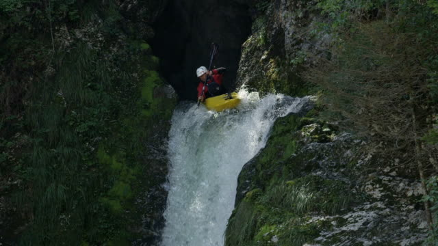 vidéos et rushes de slow motion : sportsman pagayer son canot à travers rage cascade d'eau vive - kayak sport