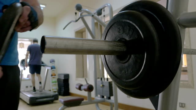 Sportsman putting disk weight on the barbell in gym video