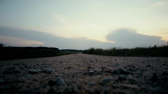 sportsman kör mot landsbygdens sunset panorama. frihet. bakifrån på lugn höst väg. filmiska slutar stadig skott - jogging hill bildbanksvideor och videomaterial från bakom kulisserna