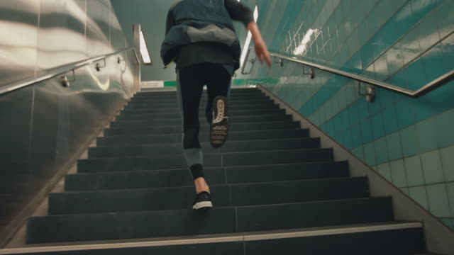 Sportsman running up on staircase at subway Low section of male athlete running up on illuminated staircase. Slow motion shot of young man is wearing sports shoes. Handheld shot of sportsman is jogging at subway. moving up stock videos & royalty-free footage