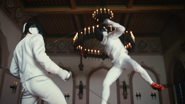 sportsman striking rival with epee sword - agilità video stock e b–roll