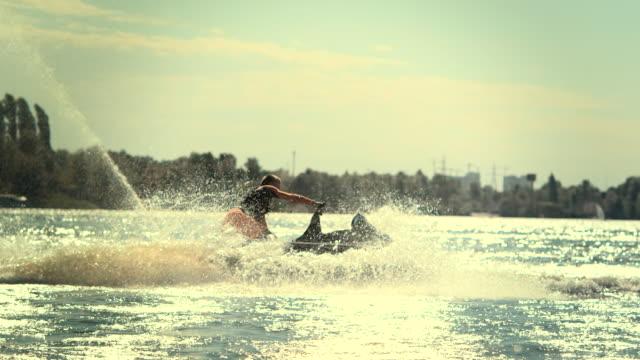 Sportsman swirling on speedy jet ski at sunset in slow motion