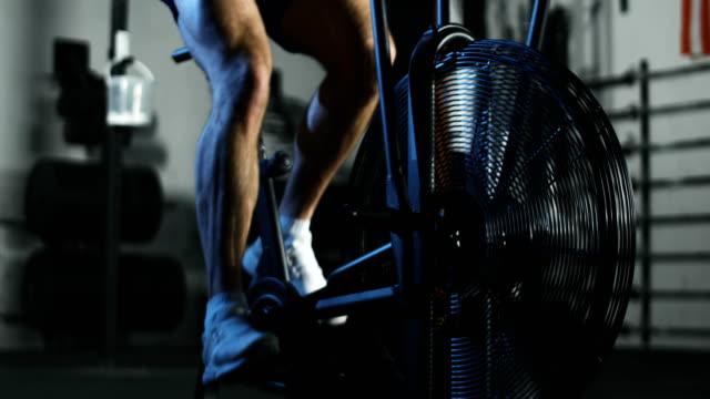 stockvideo's en b-roll-footage met sportman opleiding in lucht fiets - fitnessapparaat