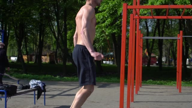sportsman training jump exercise on skipping rope. athletic man jumping with skipping rope on street workout. slow motion. - man city exercise abs video stock e b–roll