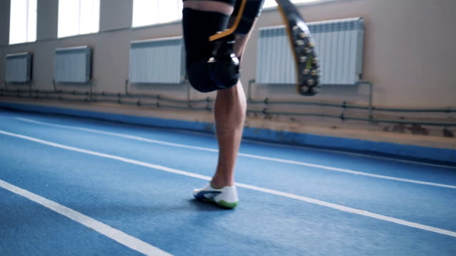 Sportsman with bionic leg jogging on a track, side view. A person with prosthesis training on a track. prosthetic equipment stock videos & royalty-free footage
