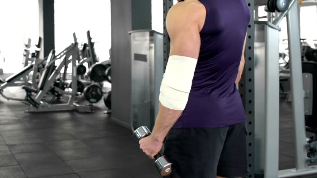Sportsman with injured elbow slowly raising dumbbell, recovery, health problem video