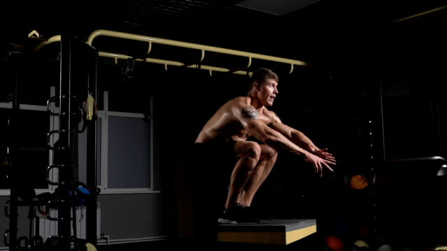 Sportsman working out his body in box jumping