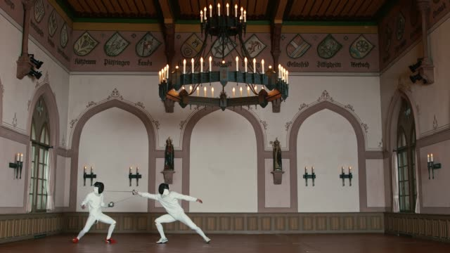 Sportsmen fighting with epee swords in castle Sportsmen fighting with epee swords. Active male athletes are training fencing in castle. They are dueling while wearing protective sportswear. rivalry stock videos & royalty-free footage