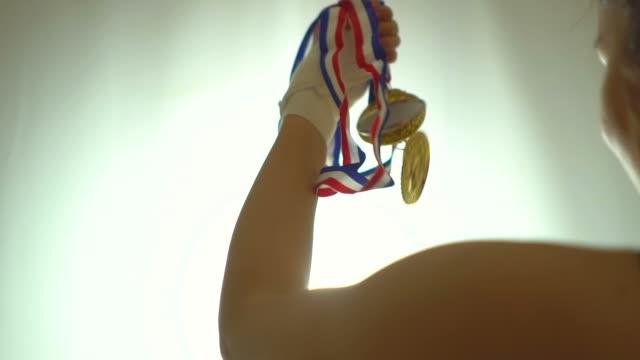 sportswoman celebrating her win with gold medals - współzawodnictwo wydarzenia filmów i materiałów b-roll